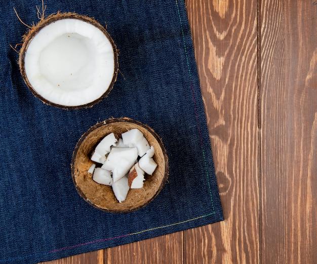 Взгляд сверху неполноценного кокоса с кусочками кокоса в раковине на джинсовой ткани и деревянной предпосылке с космосом экземпляра