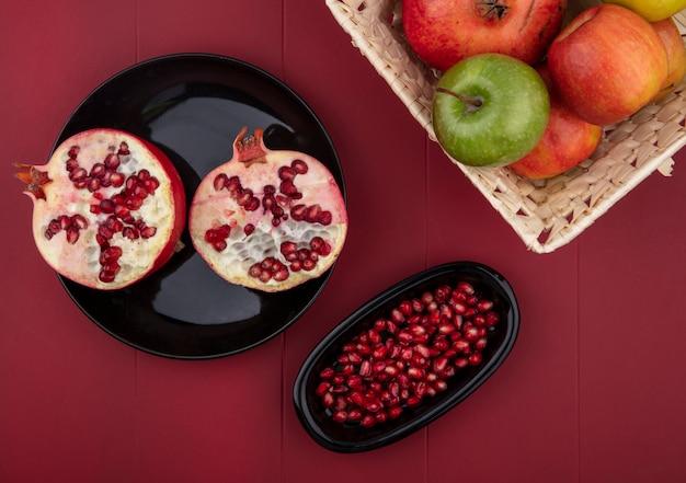 Вид сверху на половину нарезанных гранатов и ягод граната в тарелках с целой корзиной и яблоком на красной поверхности