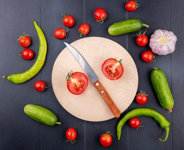 Вид сверху на половину разрезанного помидора и ножа на разделочной доске с перцем, помидором и чесноком на черной поверхности