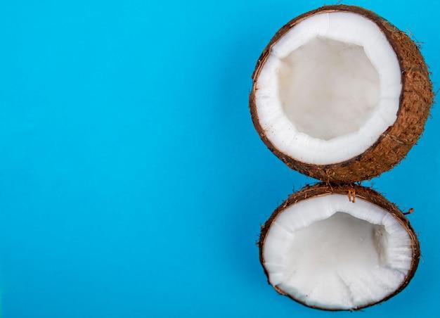 Вид сверху половины свежих больших кокосов на синей поверхности