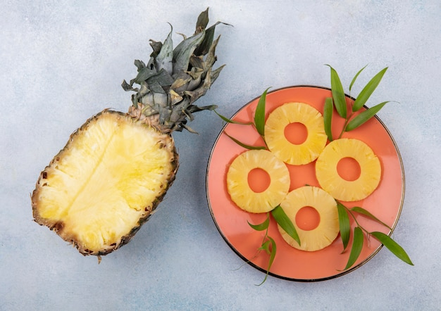 Вид сверху на половину ананаса с ломтиками ананаса в тарелке на белой поверхности