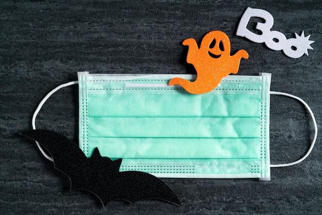 マスクとダークブラックのスレートの背景にハロウィーンのコンセプト装飾不織布の上面図。