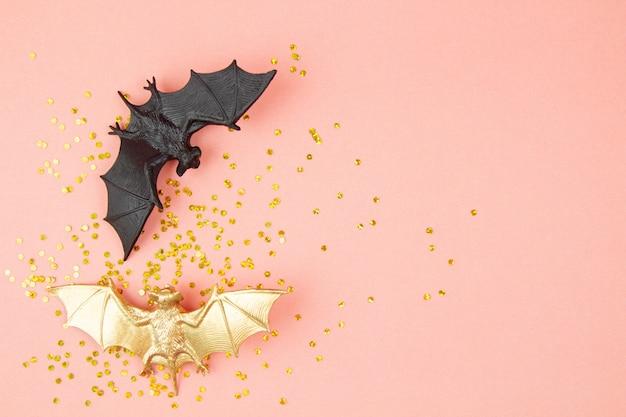 ピンクの背景の上のプラスチック製のコウモリとハロウィーンの装飾の平面図です。