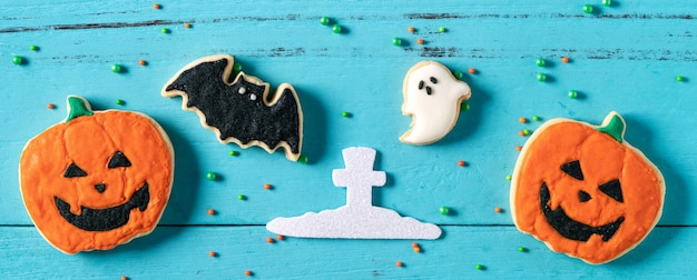 コピースペースとフラットレイで青い背景にハロウィーンのお祝いの装飾が施された焼きたてのアイシングジンジャーブレッドシュガークッキーの上面図。
