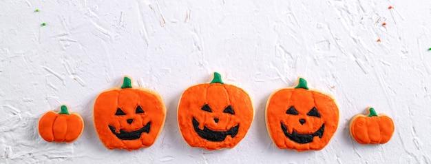 コピースペースとフラットレイレイアウトで白い背景にハロウィーンのお祝いの装飾が施されたアイシングジンジャーブレッドシュガークッキーの上面図。