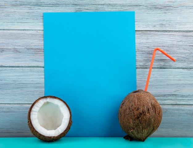 灰色の木製の表面に半分にされたココナッツと全体のココナッツのトップビュー