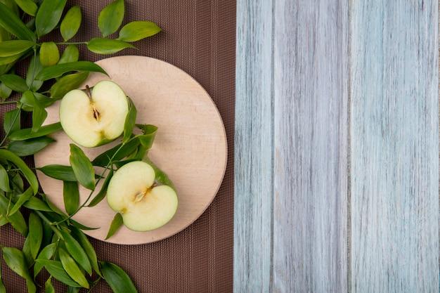 灰色の表面に葉の枝を持つスタンドに青リンゴの半分の平面図