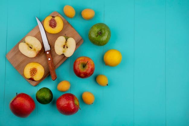 水色の表面にナイフアプリコットとライムとレモンで黒板にリンゴの半分と桃の半分の平面図