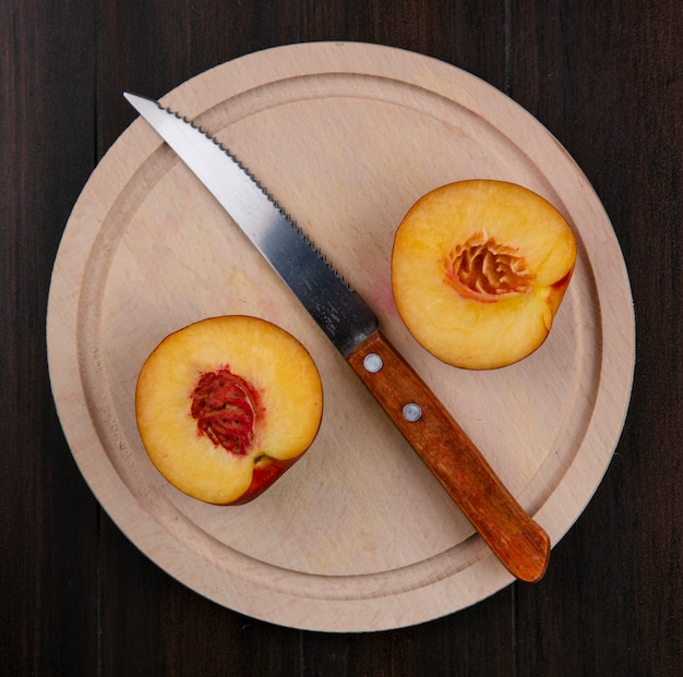 Вид сверху половинки персиков на подставке с ножом на деревянной поверхности