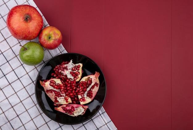 Вид сверху половинки граната на черной тарелке с цветными яблоками на клетчатом полотенце на красной поверхности
