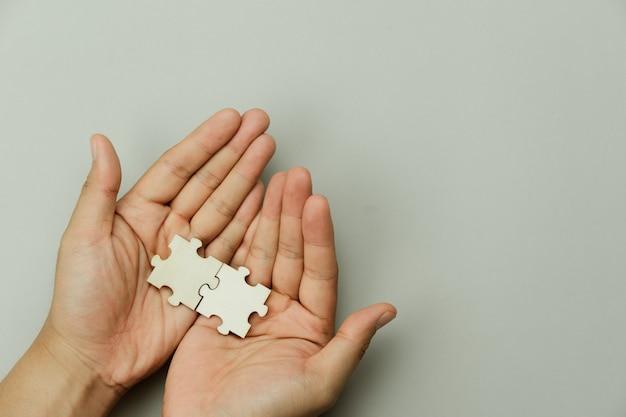 빈 퍼즐 조각을 들고 손 사업가의 상위 뷰. 팀워크의 성공과 전략.