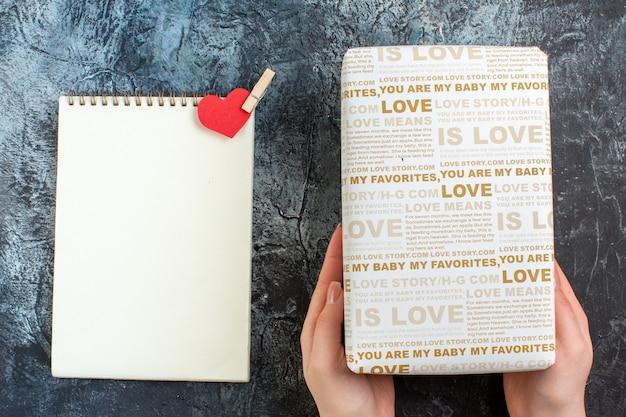 愛する人のための美しいギフトボックスと空きスペースのある暗い表面にスパイラルノートを持っている手の上面図