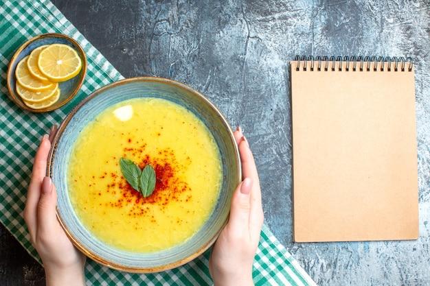 青の背景に刻んだレモン スパイラル ノートの隣にミントとコショウを添えたおいしいスープが入った青い鍋を持っている手の平面図