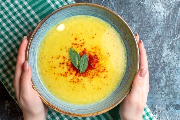 青い背景にミントとコショウを添えたおいしいスープが入った青い鍋を持っている手の平面図