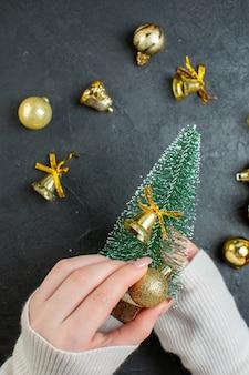 어두운 테이블에 크리스마스 트리와 장식 액세서리를 들고 손의 상위 뷰