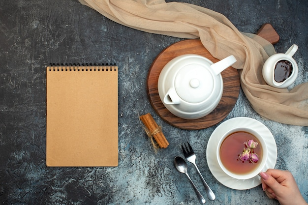 Вид сверху руки, держащей чашку черного чая и чайник на деревянной доске ноутбука на фоне льда