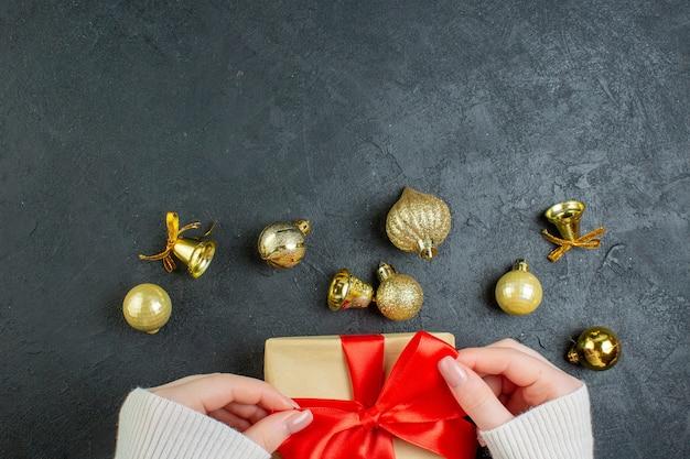 Вид сверху руки, держащей подарочную коробку с красной лентой и украшениями на темном столе