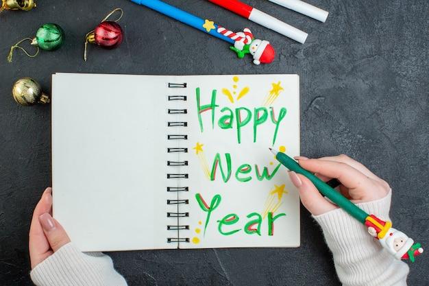 黒いテーブルに装飾アクセサリーを書く新年あけましておめでとうございますとスパイラルノートにペンを持っている手の上面図