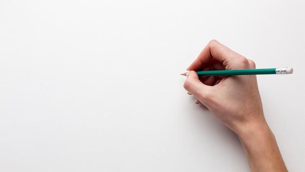 Вид сверху рука держит карандаш с копией пространства