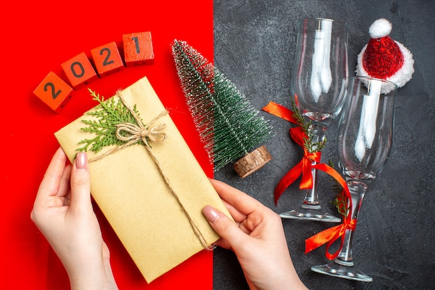 Вид сверху на руку, держащую красивый подарок, рождественскую елку, шляпу санта-клауса на красном и черном фоне