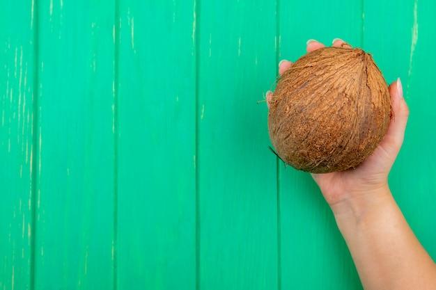 Вид сверху руки, держащей кокос на зеленой поверхности