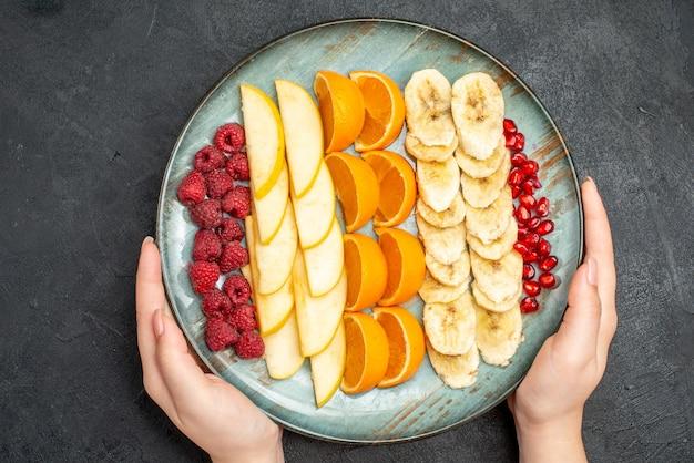 黒いテーブルの上の青いプレートに刻んだ新鮮な果物のコレクションを手に持っての上面図