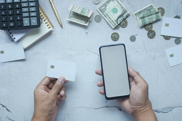 Вид сверху руки, держащей кредитную карту и использующей смартфон для покупок в интернете