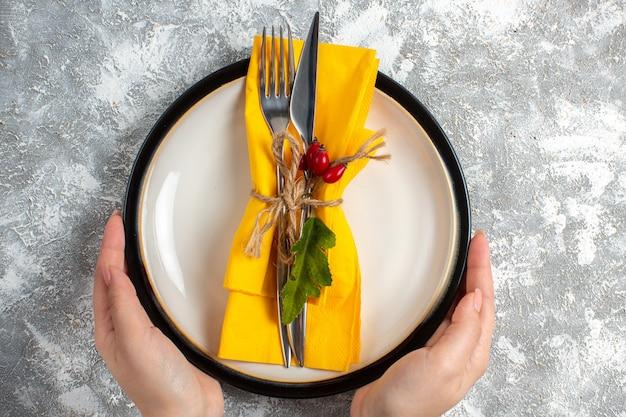 Вид сверху руки, держащей набор столовых приборов для еды на белой тарелке на поверхности льда