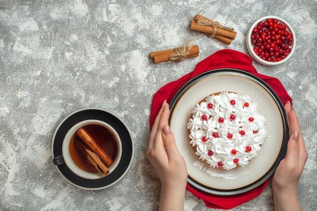 赤いタオルの上に果物で飾られたおいしいクリーミーなケーキを持っている手の平面図