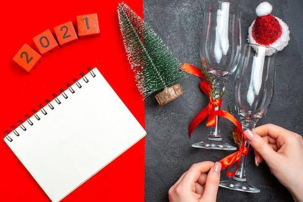 Вид сверху руки, держащей стеклянные бокалы, спиральный блокнот, рождественская елка, номера, шляпа санта-клауса на красном и черном фоне