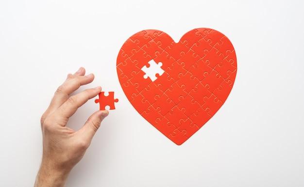 흰색 배경에 심장의 형태로 미완성 된 퍼즐 근처 마지막 조각을 들고 손의 상위 뷰