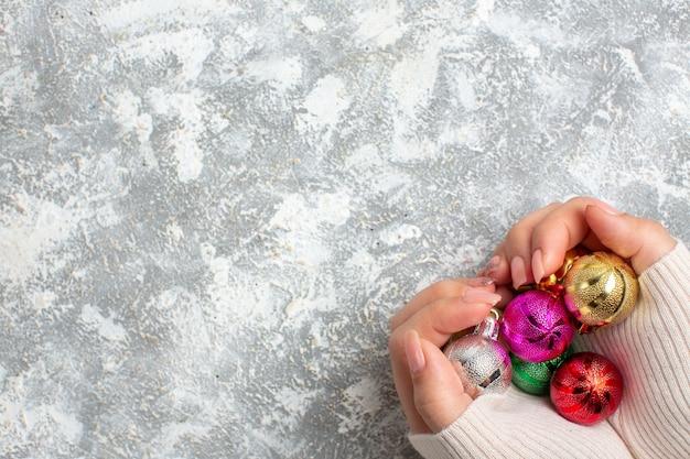 Вид сверху руки, держащей новогодние украшения с левой стороны на ледяной поверхности