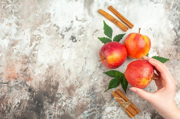 混合色の背景の左側に新鮮な天然の赤いリンゴとシナモンライムの1つを持っている手の上面図