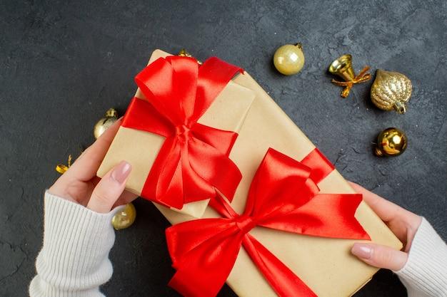 Вид сверху руки, держащей одну из подарочных коробок с красной лентой и декоративными аксессуарами на темном фоне