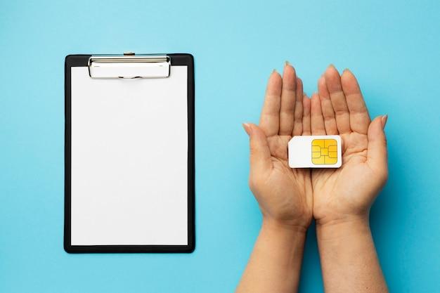 クリップボードとsimカードを持っている手の上面図