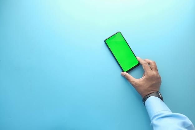 Вид сверху руки, держащей смартфон на синем фоне.