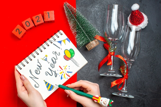 暗くて赤い背景の上の新年の図面とクリスマスツリーのガラスのゴブレット番号とスパイラルノートを持っている手の上面図