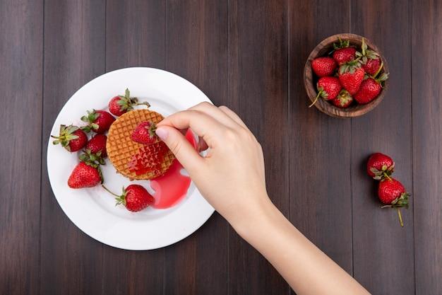 木の表面にイチゴのプレートとボウルにワッフルビスケットとイチゴを持っている手の平面図