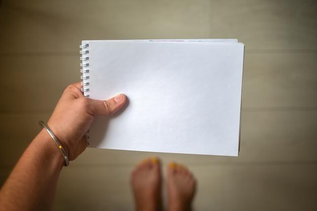 손의 위쪽 보기에는 카피스페이스가 있는 흰색 빈 종이 메모장이 있습니다.
