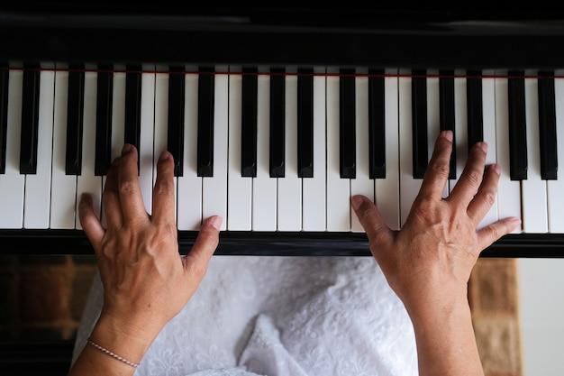 Вид сверху руки, играющей на пианино