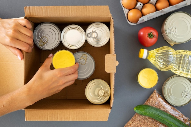 Вид сверху руки, готовящей пожертвования еды в коробке