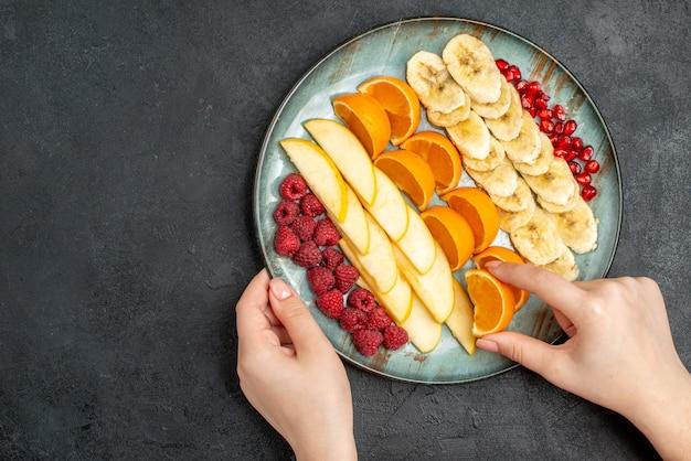 黒いテーブルの上の青いプレートに刻んだ新鮮な果物のオレンジスライスコレクションを取っている手の上面図