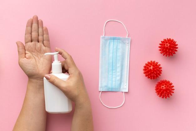Вид сверху руки, использующей жидкое мыло с медицинской маской и вирусами