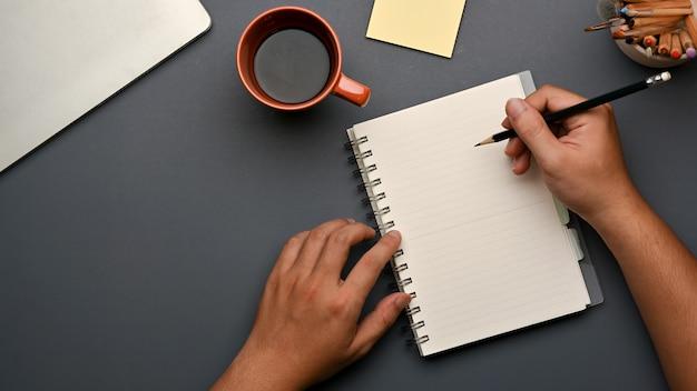 コーヒーカップと文房具とワークスペースの空白のノートに手書きの上面図