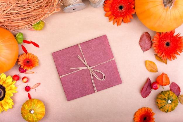 Взгляд сверху подарочной коробки ручной работы, желтых и оранжевых цветков и тыкв на розовой предпосылке. пустая открытка для творческого дизайна работы. плоская планировка.