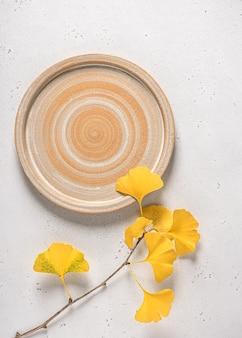 흰색 은행 나무 분기와 수제 노란색 세라믹 접시의 상위 뷰