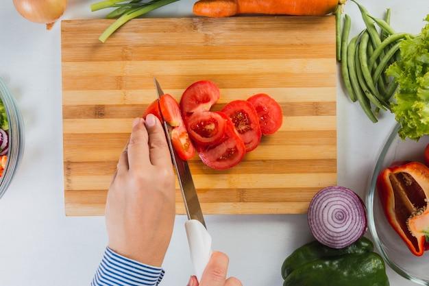 신선한 토마토를 절단하는 손의 최고 볼 수 있습니다.