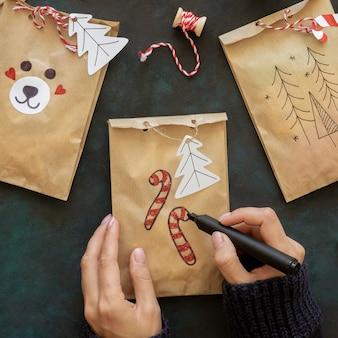 Вид сверху рук, украшающих рождественские подарочные пакеты