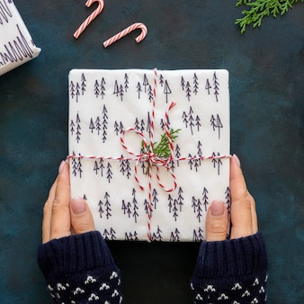 美しく装飾されたクリスマスプレゼントを持っている手の上面図