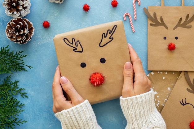 Вид сверху на руки, держащие милых оленей, украшенных рождественским подарком